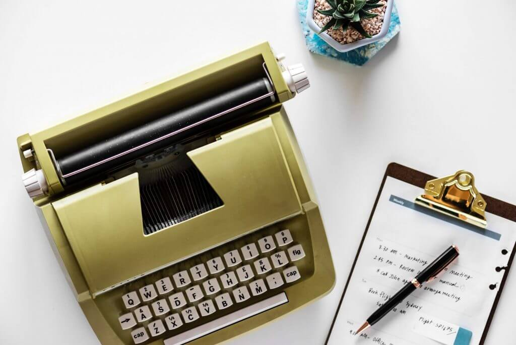 Content Writing Process Image in Outsource Workers - Yellow Green Typewriter and Note Taking Pad